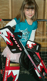 Smiling girl in tutu and indoor goalie hockey gear